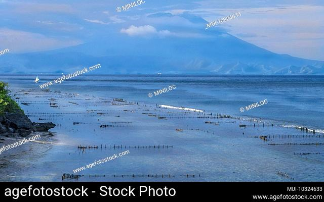 Beautifull evening view to St. Agung Vulcano on Bali from Nusa Penida Island. Partly Covered by Clouds. Indonesia