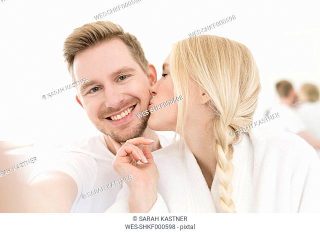 Man taking selfie of girlfriend kissing him
