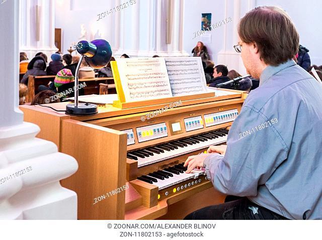 Samara, Russia - February 25, 2018: Man playing on the electronic organ at the Roman Catholic parish of the sacred Heart of Jesus