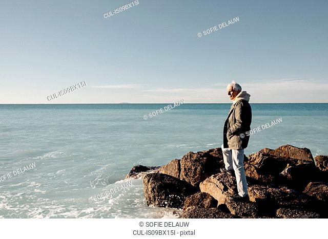 Senior man looking out to sea, Livorno, Italy