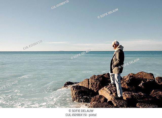 Senior man looking out to sea, Livorno, Italy