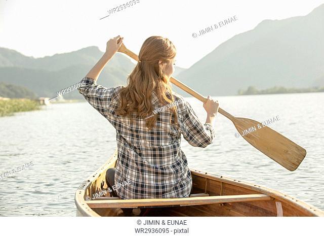 Back of female traveler paddling canoe