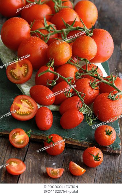 Vine tomatoes on a dark wooden board, whole and sliced