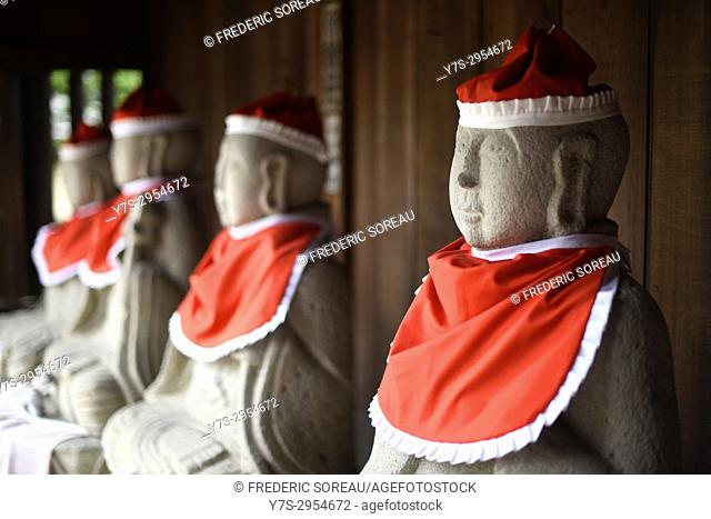 Statuettes wearing red woolen hats outside a Buddhist temple in Takayama, Japan, Asia