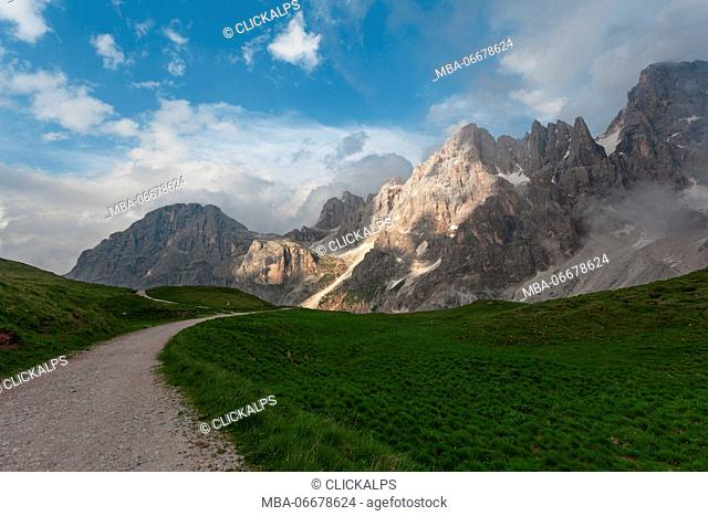 Path through the meadows near the Baita Segantini. In the background the mountain Mulaz and the spiers of the Pale di San Martino