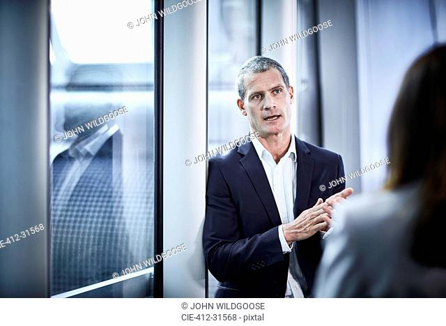 Businessman talking to businesswoman in office