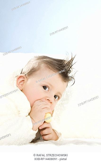 Baby in dressing gown eating crisp