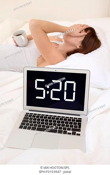 MODEL RELEASED. Exhausted woman in bed with laptop and coffee