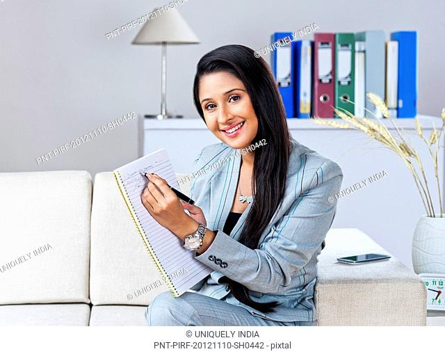 Businesswoman sitting on a couch and writing on a notebook