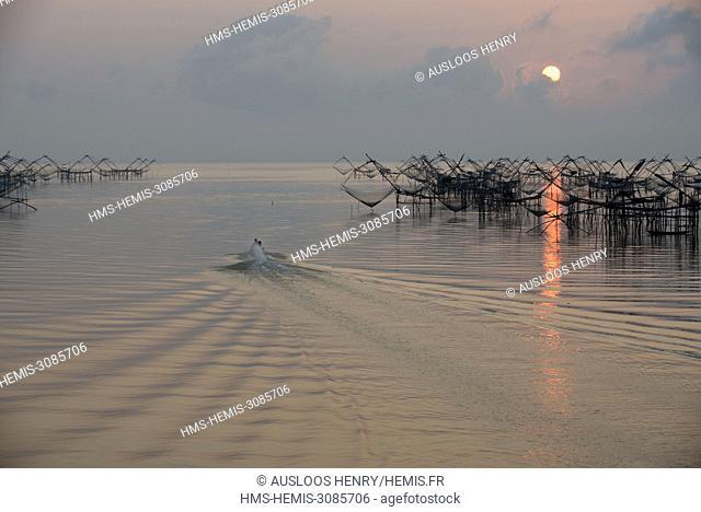 Thailand, Phatthalung, Shore-operated lift net, Fishermen on boat, Sunrise