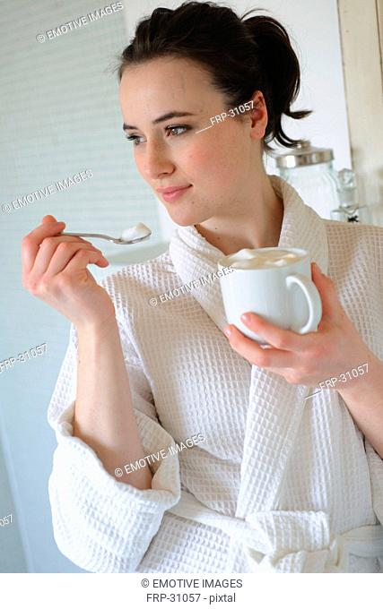 Young woman drinking coffee in bathroom