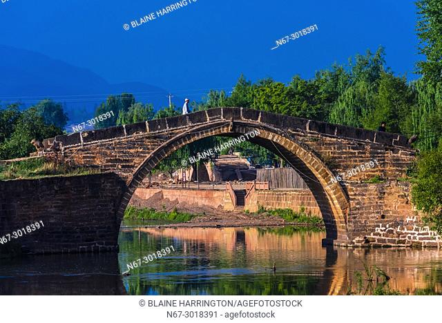 A beautiful arched bridge on the outskirts of the market town of Shaxi, on the Tea Horse Caravan Road, which links Southern Yunnan to Tibet and Burma and...