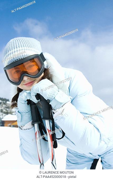 Teen girl leaning on ski poles, smiling at camera