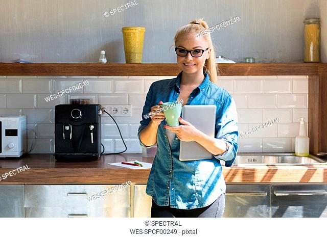 Portrait of smiling businesswoman standing with coffee mug and tablet in the kitchen