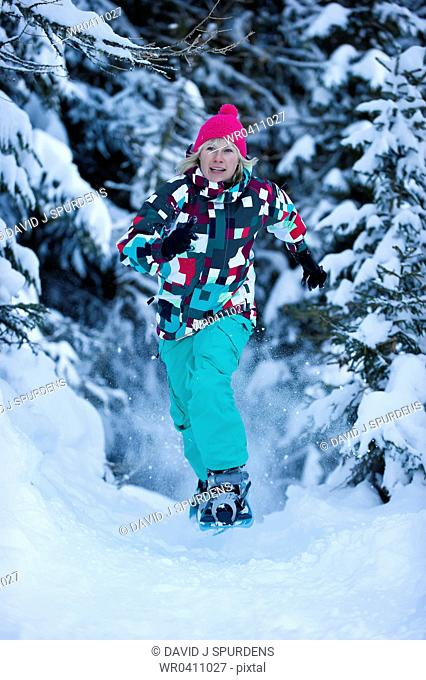 A woman snowshoeing through a snowy forest