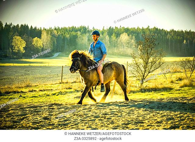 Young adult riding a horse in Sweden