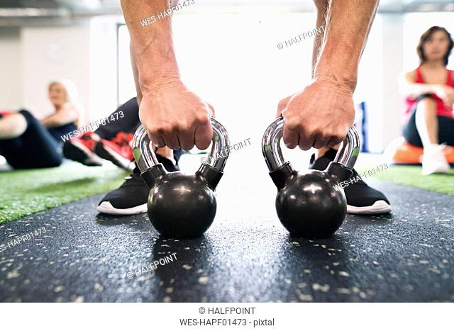 Close-up of man exercising with kettlebells in gym
