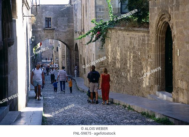 Tourists walking in lane of town, Palace of the Grand Master of the Knights, Rhodes, Dodecanese Islands, Greece