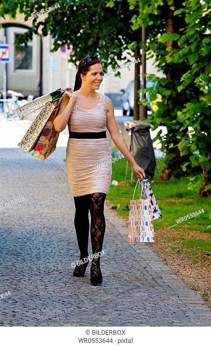 A young woman shopping with many shopping bags