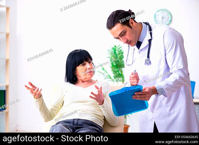 The young doctor examining senior old woman