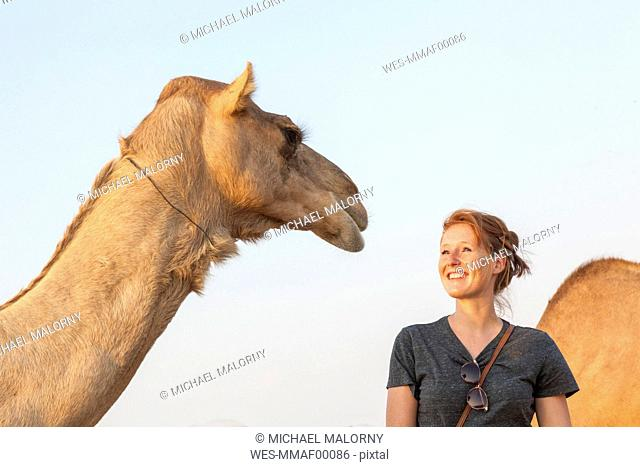 UAE, happy woman looking at a camel