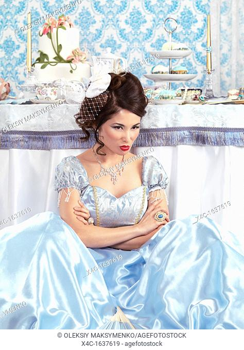 Beautiful asian lady with a sulky pout sitting on the floor besid a party table