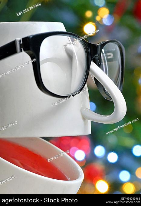 Conceptual Teacup with Eyeglasses Laughing with holidays background