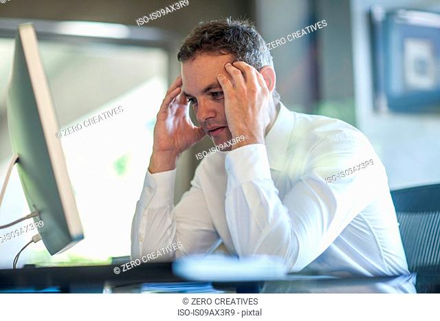 Stressed businessman with hands on forehead at office desk