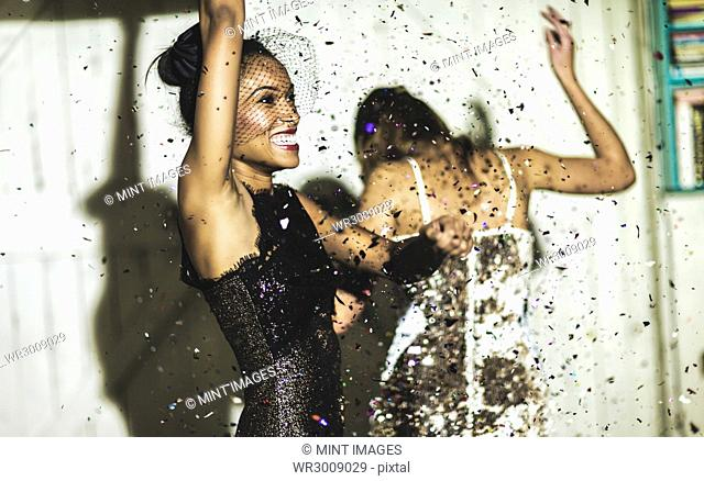Two women wearing cocktail dresses at a party dancing in a shower of glitter confetti