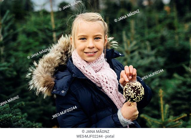 Little girl standing in front of fir trees holding chocolate dipped apple