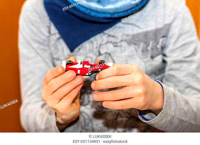 Little boy showing his model racing car