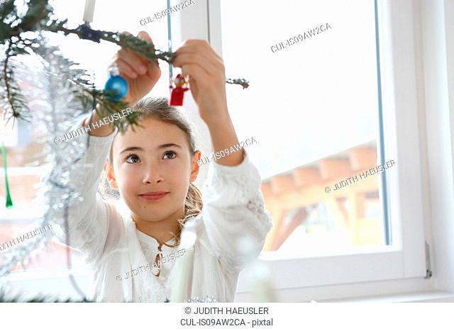 Girls arms raised adding christmas decoration to christmas tree