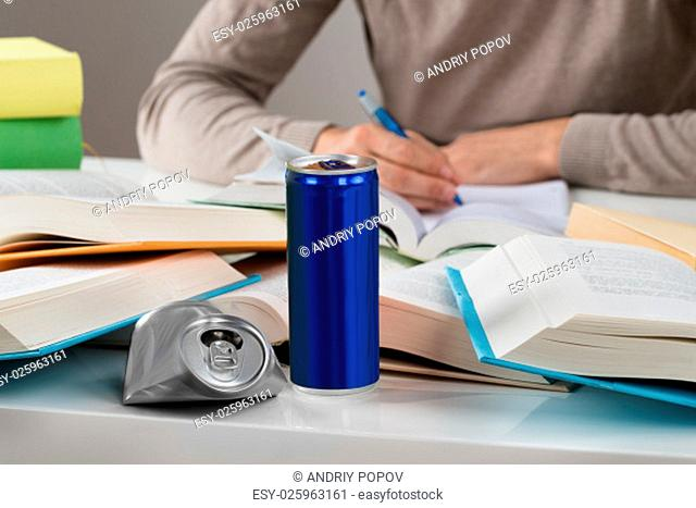 Midsection of male student studying with crashed drink can and books at table