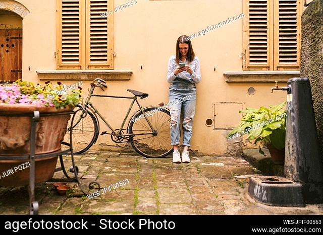 Smiling young woman standing at a house using smartphone, Greve in Chianti, Tuscany, Italy