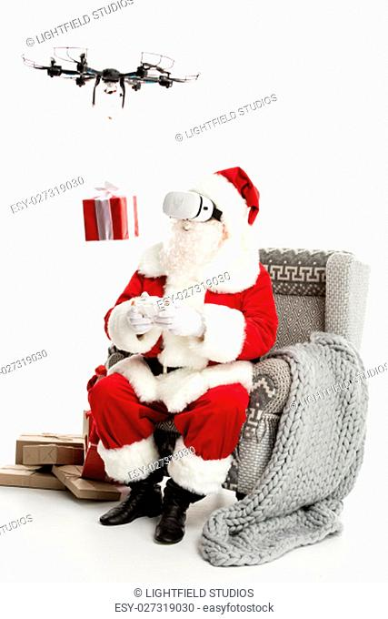 Santa Claus, sitting on grey armchair, wearing virtual reality headset, using hexacopter drone