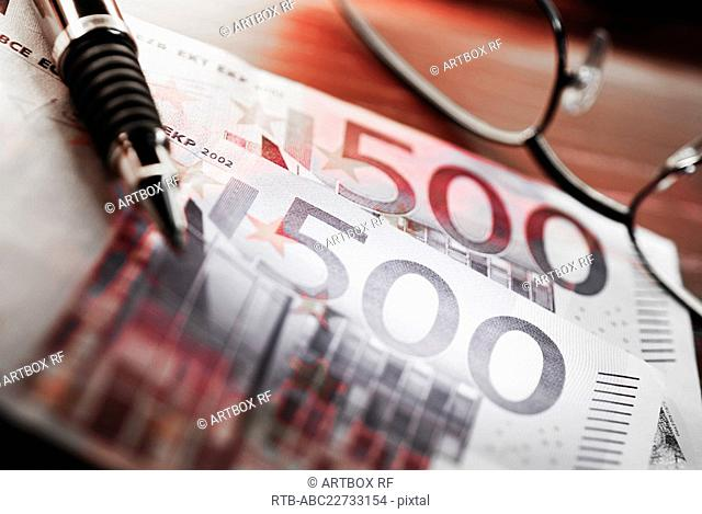 Close-up of a pen and eyeglasses on Euros