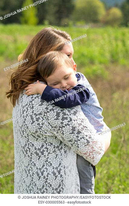 Realistic lifestyle portrait of a mother and her son together outdoors in a natural field in Oregon