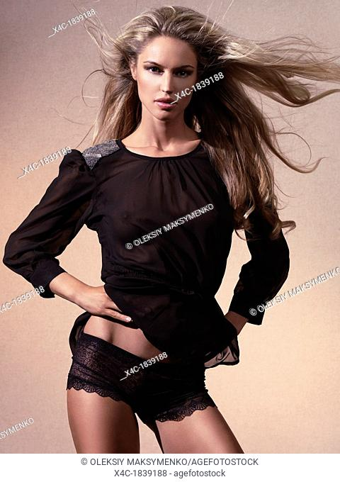 Fashion photo of young beautiful woman wearing black underwear lace boy shorts and a see-through top on beige background