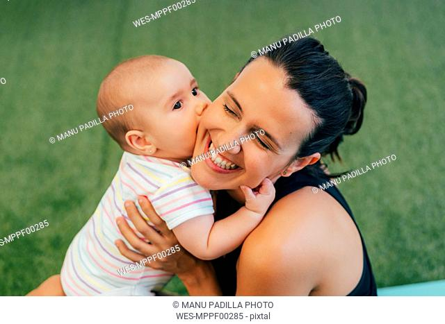 Young mother and baby during yoga exercise, kiss