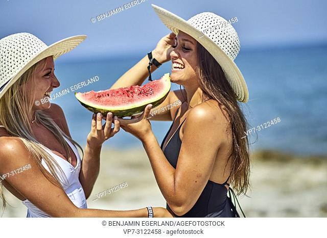 Two young women with water melon and sunhats. Chersonissos, Crete, Greece