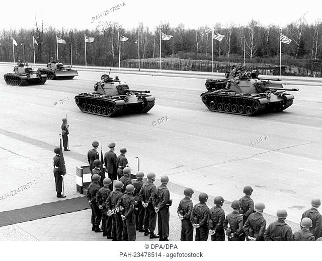 American tanks driving past a VIP stand during a parade to the farewell of General Bruce C. Clarke on 6th April 1962 in Berlin
