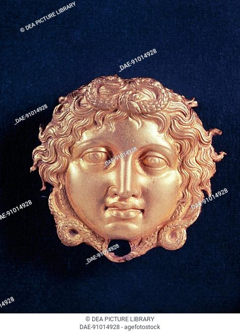 Greek civilization, 4th century b.C. Goldsmithery. Gold wall lamp shaped as Medusa's head. From Vergina, Royal Tombs.  SALONIKA