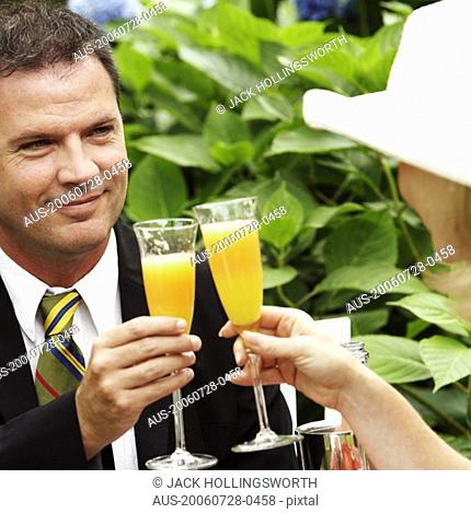 Close-up of a couple toasting glasses of juice