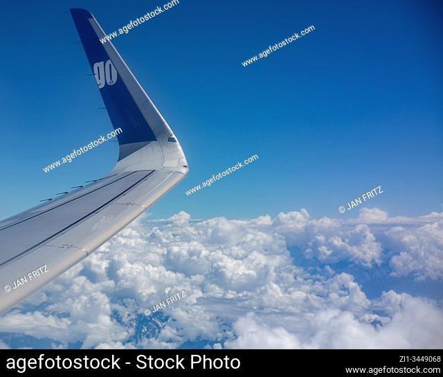 aerial view of clouds and blue sky with wing from plane