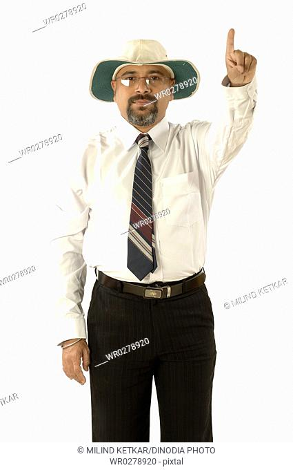 South Asian Indian cricket umpire indicating out sign by raising index finger above head MR705G