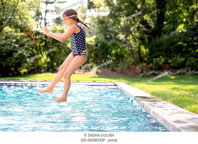 Girl jumping into outdoor swimming pool