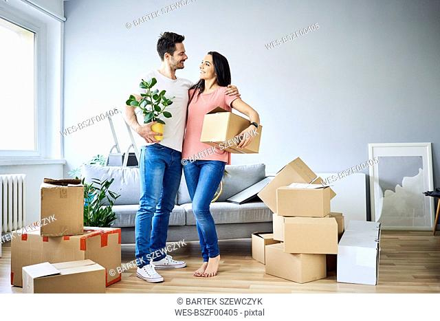 Happy couple unpacking in new apartment
