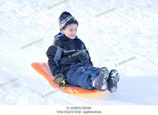 Little boy sleigh rides in fresh snow near Lexington, Ma., New England, USA