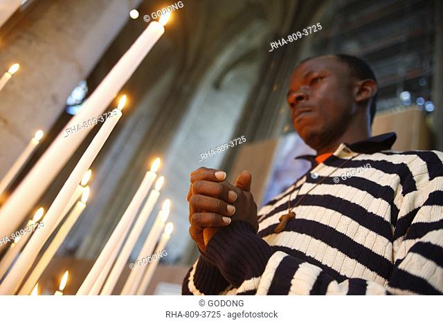 Man praying with candles in church, Amiens, Somme, France, Europe