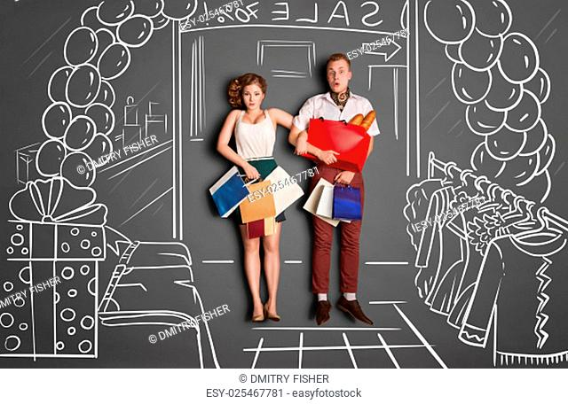 Love story concept of a romantic couple on shopping against chalk drawings background. Young couple with shopping bags entering a shopping mall during sales